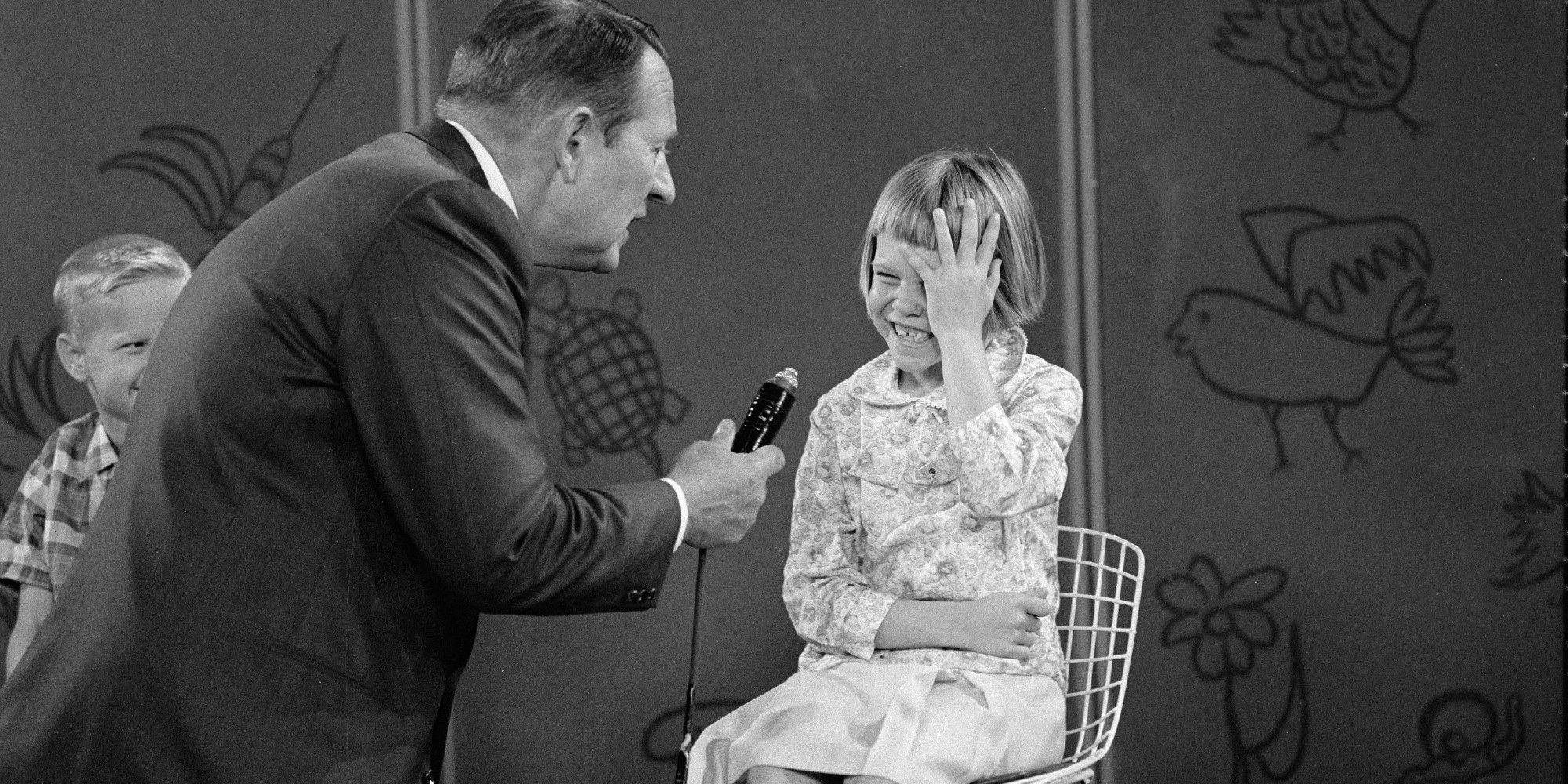Canadian-born television host Art Linkletter (born Arthur Gordon Kelly) holds the microphone as he interviews an unidentified, laughing girl on an episode of the 'Kids Say the Darndest Things' segment of 'Art Linkletter's House Party,' April 23, 1965. (Photo by CBS Photo Archive/Getty Images)